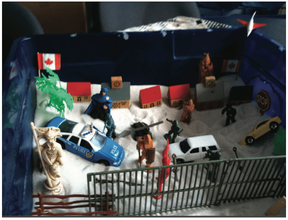 This sand tray, dominated by symbols of violence, security and barricades, was created by a 12-year-old boy while he was detained with his mother and older sister. The family's asylum claim was refused and, at the time of the interview in 2011, they had been detained at the IHC for seven months. The boy appeared to have developed multiple psychiatric symptoms during detention. © Rachel Kronick